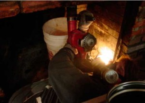 Chipping hammer being used in fireplace to make room for liner to fit thru to connect directly onto wood stove insert
